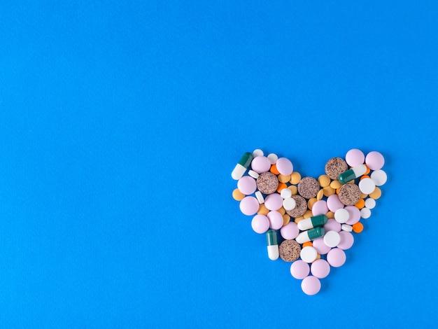Hart gemaakt van kleurrijke pillen op blauw.
