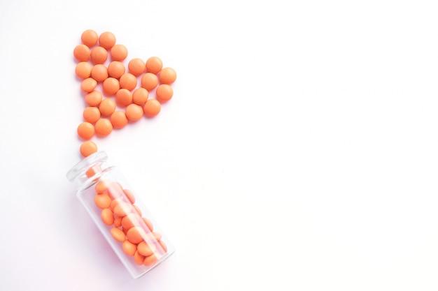 Hart gemaakt van oranje tabletten en glazen fles op wit