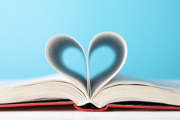 Hart gemaakt van pagina's. boek tegen blauwe achtergrond, ruimte voor tekst