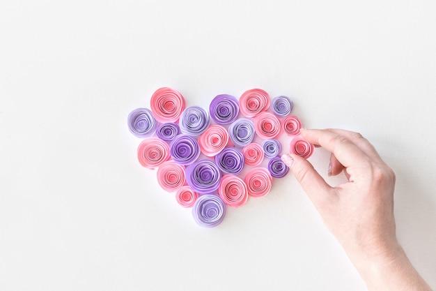 Hart gemaakt van papieren roze en lila bloemen met de hand van de vrouw