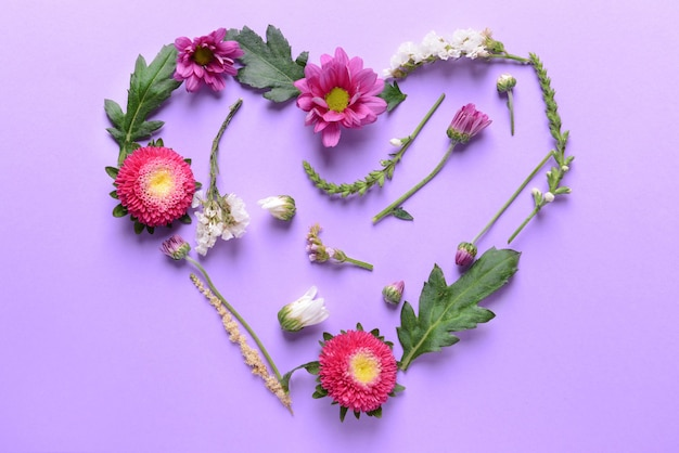 Hart gemaakt van prachtige bloemen en bladeren op paarse achtergrond