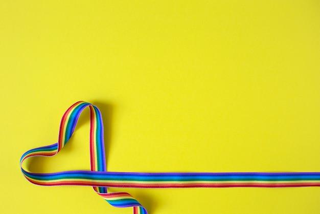 Hart gemaakt van regenboog lint op een gele achtergrond. lgbt-concept