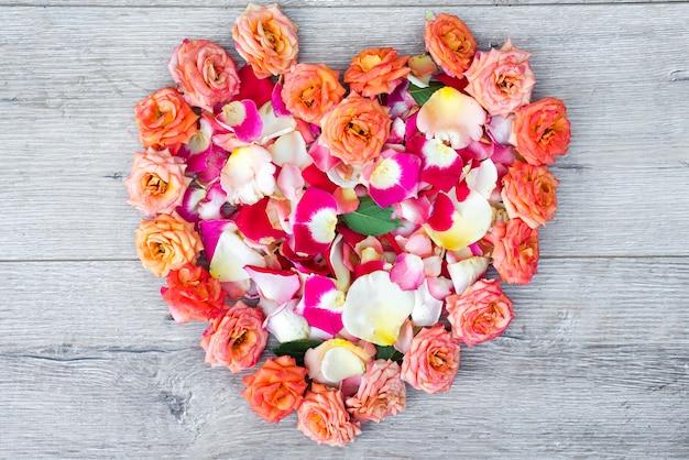 Hart gemaakt van roze bloemen op houten achtergrond voor valentijnsdag.