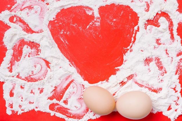 Hart gemaakt van tarwemeel op een rode achtergrond. keuken en voedselbereiding voor de vakantie.