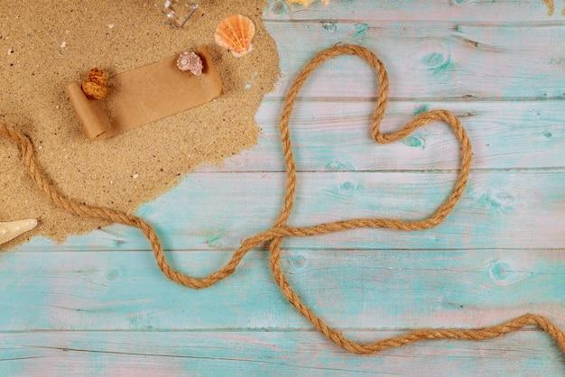 Hart gemaakt van touw op kust met schelpen