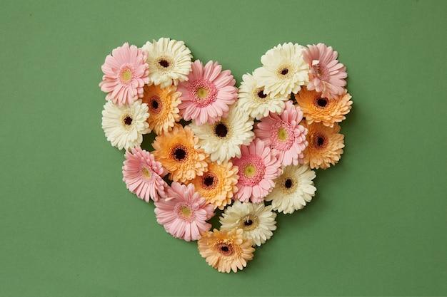 Hart gemaakt van verse gerberabloemen op een groene achtergrond. st. valentijnsdag plat lag kopieerruimte