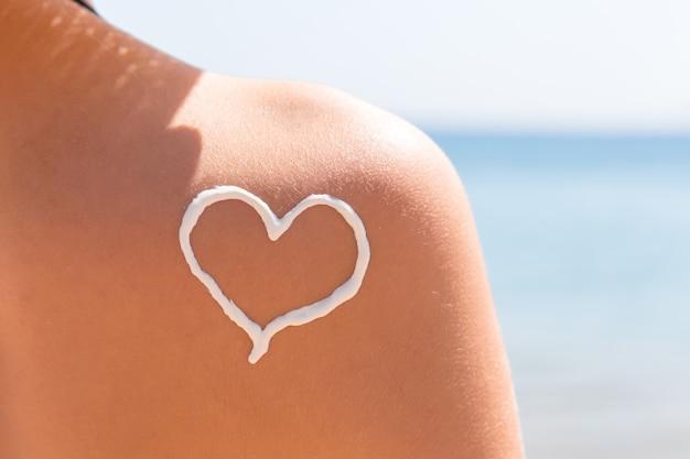 Hart gemaakt van zonnebrandcrème is getekend op de schouder van de vrouw op het strand.