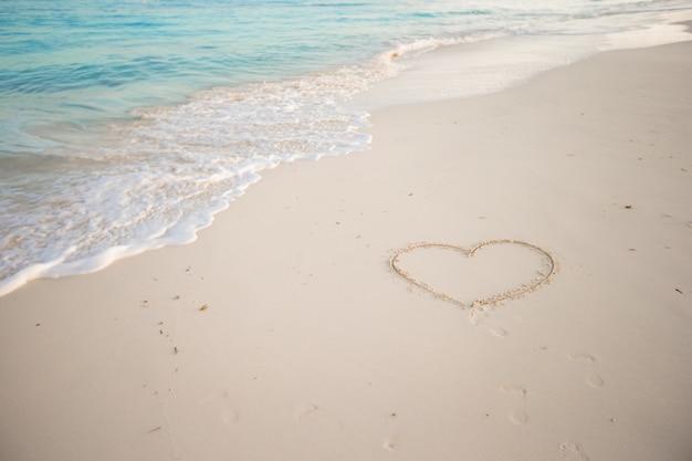 Hart geschilderd in wit zand op een tropisch strand