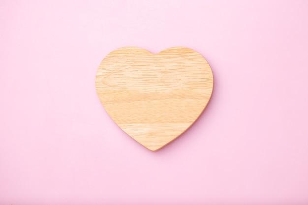 Hart houten leeg voor bericht op roze achtergrond, moederdag en valentijnsdag concept