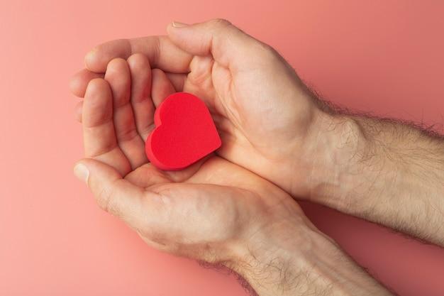 Hart in de handen van een vrouw op een gekleurde achtergrond. achtergrond voor valentijnsdag (14 februari) en liefde.
