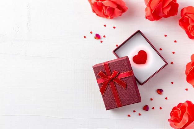 Hart in de open geschenkdoos voor valentijn in de buurt van bloemen op witte houten achtergrond schijnt