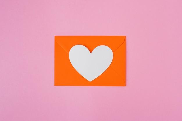 Hart in een envelop op een oranje achtergrond.