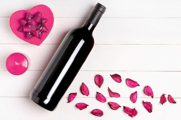 Hart, kaars, wijnfles, bloemen op witte houten oppervlak. valentijnsdag concept. plat lag, bovenaanzicht