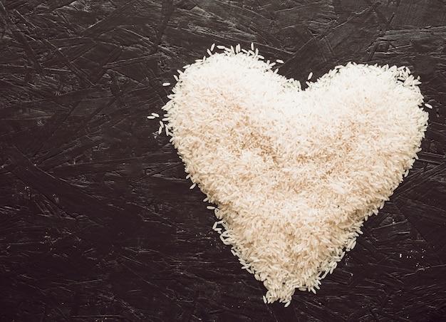 Hart met rijstkorrels op geweven achtergrond wordt gemaakt die