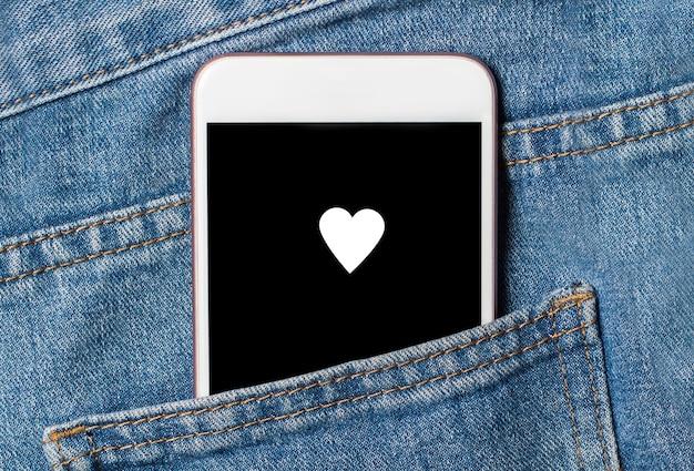 Hart op achtergrondtelefoon op jeansliefde en valentijnskaartconcept