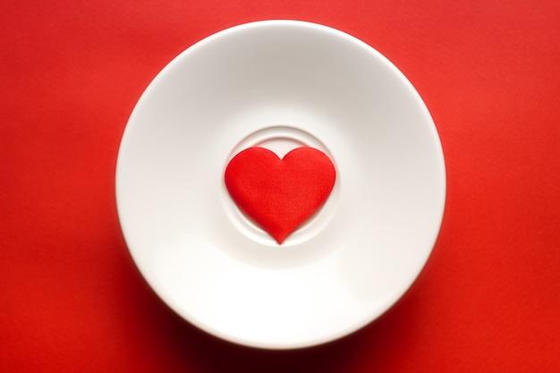 Hart op witte schotel bij rode achtergrond. romantiek en liefde concept.