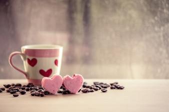 Hart roze koekjes en koffiekopje op regenachtige dag venster achtergrond in vintage kleurtoon