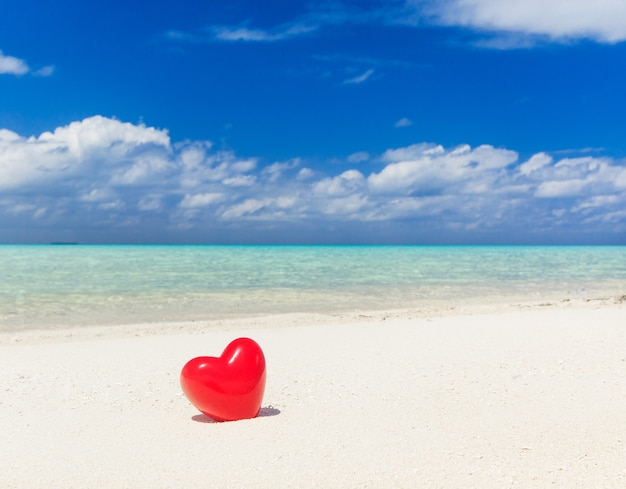 Hart speelgoed in het strand, liefde, zomervakantie en huwelijksreis concept.