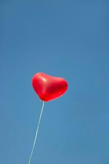 Hart valentijn rode ballon als symbool van liefde voor valentijnsdag in de blauwe lucht