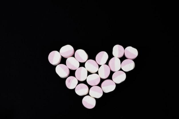 Hart van marshmallow snoepjes op een zwarte achtergrond. detailopname