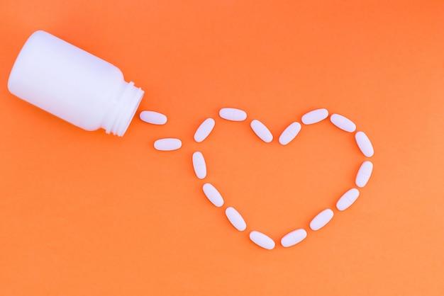 Hart van pillen op een oranje achtergrond. tabletten zijn bezaaid in de vorm van een hart uit een wit blikje medicijnen. plat liggen.