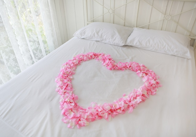 Hart van rode bloemblaadjes op een bed