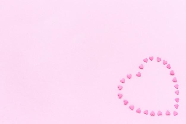Hart van roze zoetwaren hagelslag in hartvorm gelegen in de rechterhoek op pastel roze achtergrond.