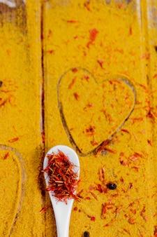 Hart van specerijen en kruiden. witte lepel met saffraan op kerrieachtergrond. verschillende kruiden selectie. detailopname. kopieer ruimte. liefde
