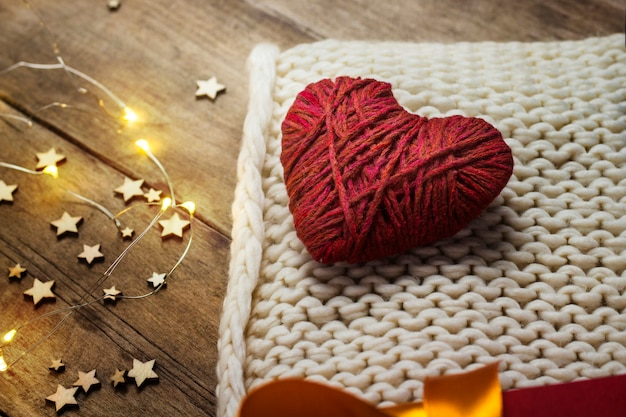 Hart van stof, gebreide sjaal, geschenkdozen, lichtgevende slinger op een houten achtergrond.