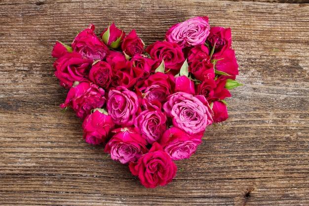 Hart van verse roze rozenknoppen die op witte achtergrond worden geïsoleerd