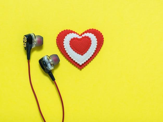 Hart van witte en rode kleuren in oortelefoons op gele achtergrond. weergegeven afbeelding. plat leggen afgezwakt.