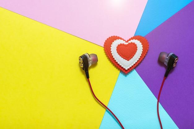 Hart van witte en rode kleuren in oortelefoons op kleurrijke achtergrond. weergegeven afbeelding. plat leggen afgezwakt.