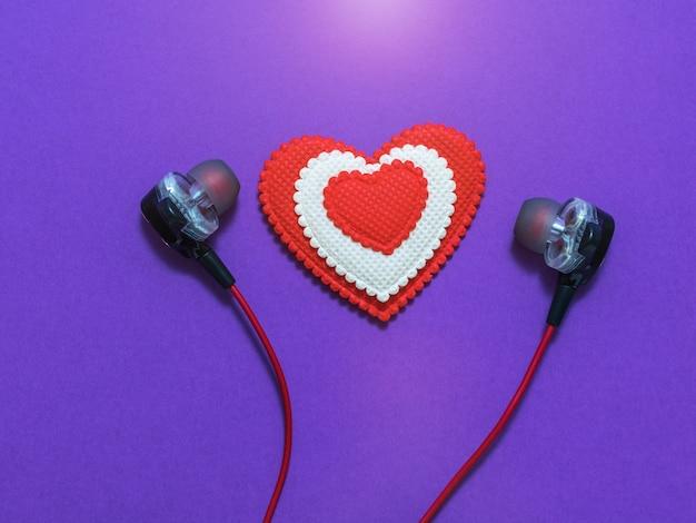 Hart van witte en rode kleuren in oortelefoons op paarse achtergrond. weergegeven afbeelding. plat leggen.