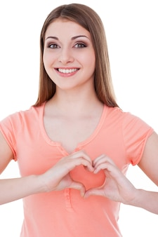 Hart vorm. mooie jonge vrouw die naar de camera kijkt en een hartvorm maakt met de handen terwijl ze op wit wordt geïsoleerd