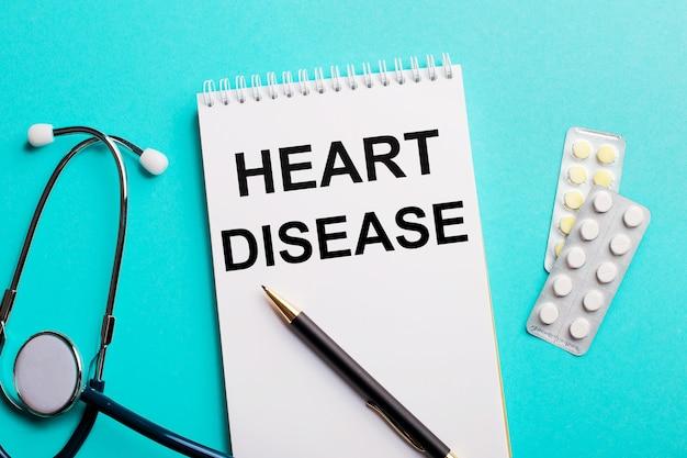 Hart-ziekte geschreven in een witte blocnote in de buurt van een stethoscoop, pennen en pillen op een lichtblauw oppervlak