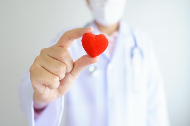 Hartcontrole arts die rood hart op handen bij ziekenhuiskantoor houdt. gezondheidszorg en medisch concept.