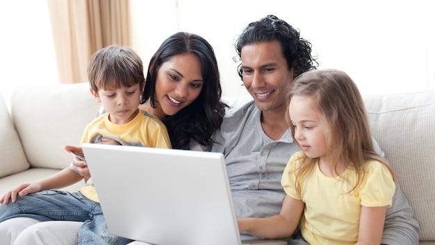 Hartelijke ouders die laptop met hun kinderen gebruiken