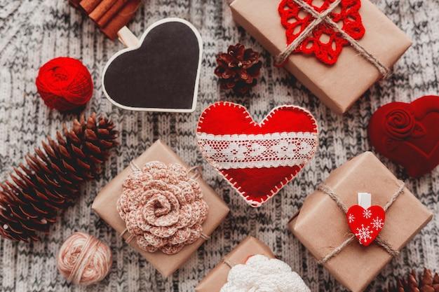 Harten, cadeautjes in ambachtelijk papier met gehaakte bloemen, dennenappels, rode sieraden geschenkdoos