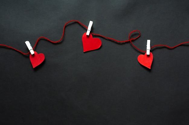 Harten die op koord op een zwarte achtergrond hangen. valentijns achtergrond