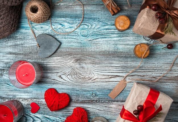 Harten en geschenkdozen met kaarsen op een houten achtergrond.
