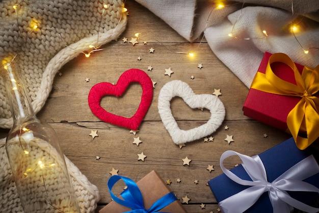 Harten, gebreide sjaal, geschenkdozen, lichtgevende slinger op een houten achtergrond.