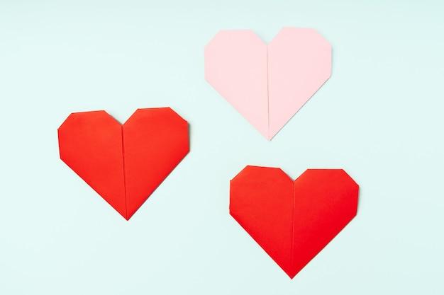 Harten gemaakt van gekleurd origami papier op een achtergrond bovenaanzicht en plaats voor tekst love concept