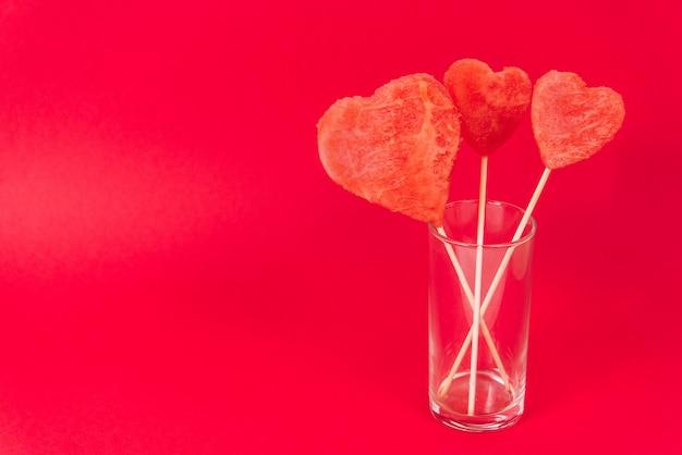 Harten gemaakt van watermeloenpulp op een houten stok. creatieve valentijnsdag kaart.