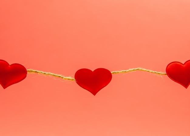 Harten op een touw op rode achtergrond