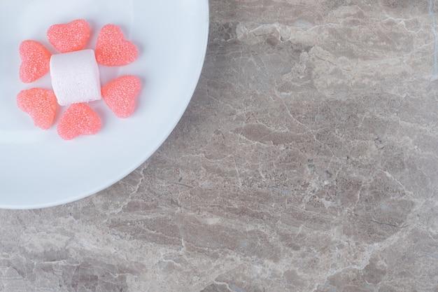 Hartgeleisnoepjes rond een marshmallow op een schaal op een marmeren oppervlak