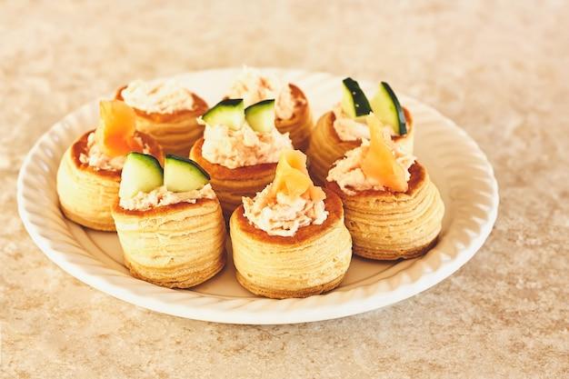 Hartig vol au vents gebak gevuld met zeevruchtencrème en gedecoreerd met zalm en komkommer.