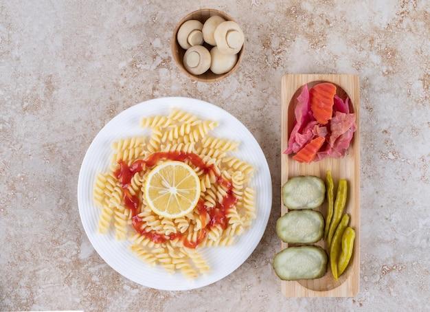 Hartige augurk dienblad en champignonkom vergezeld van pastaschotel op marmeren oppervlak.