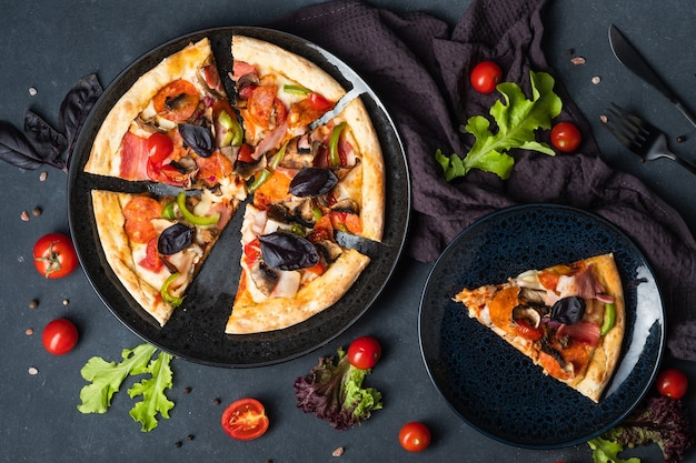 Hartige homemade meat pizza met pepperoni bacon-tomaten en basilicum op een donkere achtergrond