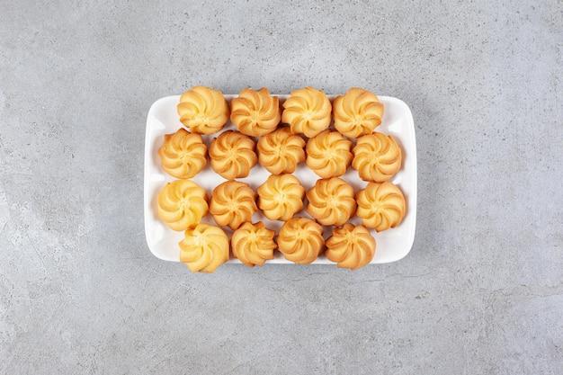 Hartige koekjes gerangschikt op een witte plaat op marmeren achtergrond. hoge kwaliteit foto