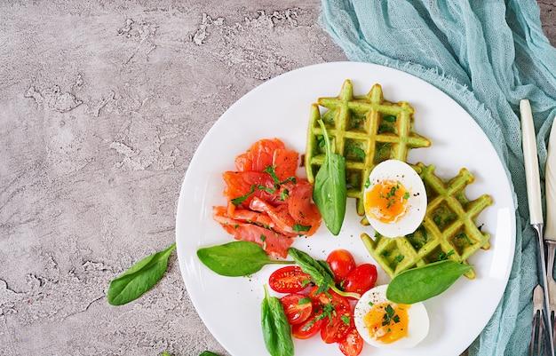 Hartige wafels met spinazie en ei, tomaat, zalm in witte plaat. smakelijk eten. bovenaanzicht. plat liggen